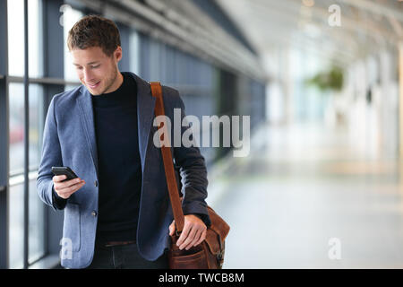 L'homme sur smart phone - jeune homme d'affaires dans l'aéroport. Professionnels urbains occasionnels businessman smiling happy smartphone immeuble de bureaux à l'intérieur ou à l'aéroport. Bel homme portant veste de costume à l'intérieur. Banque D'Images