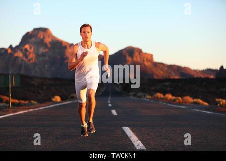 Athlete running courir au coucher du soleil sur la route. Dans la formation de canaux chauds masculins paysage de montagne dans la nuit. Fit young musculaire modèle sport dans son 20s. Banque D'Images