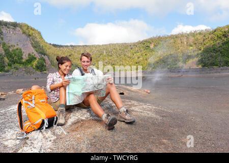 Couple hiking sur volcan de Hawaii à la carte à. Happy young man and woman relaxing prendre pause dans beau paysage nature volcanique sur Big Island à Hawaii Volcanoes National Park, USA. Banque D'Images