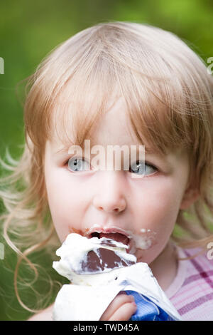 Little girl eating chocolate glace face closeup Banque D'Images