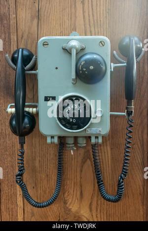 Ancien téléphone accroché sur un mur en bois close-up view Banque D'Images