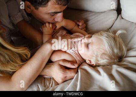 Un an smiling blonde dans une robe rose est allongé sur le canapé beige à la maison. Père embrassant les mains de babys Banque D'Images