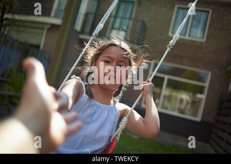POV de père jouant avec sa jeune fille dans le jardin arrière sur une balançoire dans soleil du printemps Banque D'Images