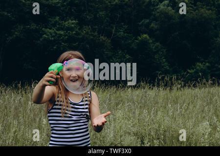 Girl blowing bubbles avec canon à bulles. Jeune enfant jouer dehors. Activités de jour d'été. Heureux, joyeux enfant à l'extérieur. Avoir du plaisir seul. Belle et pittoresque paysage forestier. Paysage pittoresque Banque D'Images