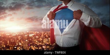 Jeune homme d'agir comme un super héros et de déchirer sa chemise sur la ville au coucher du soleil avec copie espace Banque D'Images