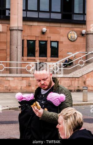 Couple avec l'homme transportant deux jeunes bébés en écharpe corps tout en mangeant un sandwich au quai de Newcastle Upon Tyne en Angleterre. Banque D'Images