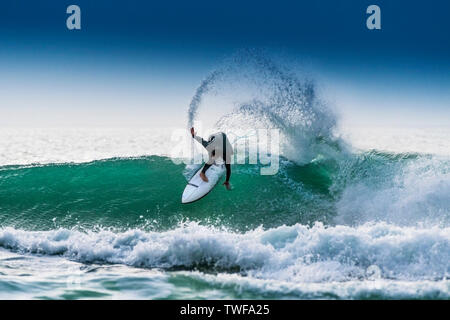 Un surfeur équitation un surf sur la crête d'une vague de couleur jade dans Fistral Newquay à à Cornwall.