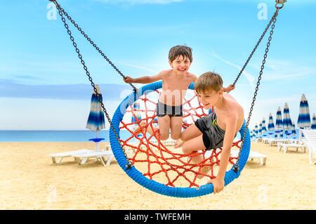 Amusant swinging sur plage, journée ensoleillée Banque D'Images