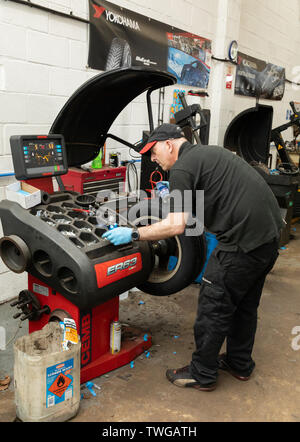 L'équilibrage des roues de voiture mécanicien après nouveau pneu a été installé. Bury Centre du pneu à Bury St Edmunds, Suffolk, UK Banque D'Images