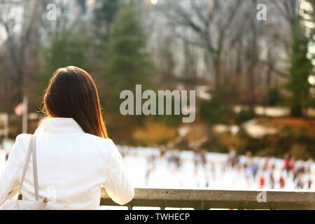 Patinoire de Central Park - femme dans la ville de New York à la fin de l'automne au début de l'hiver avec patinoire en arrière-plan. Sourire candide fille multi-ethnique sur Manhattan, USA.