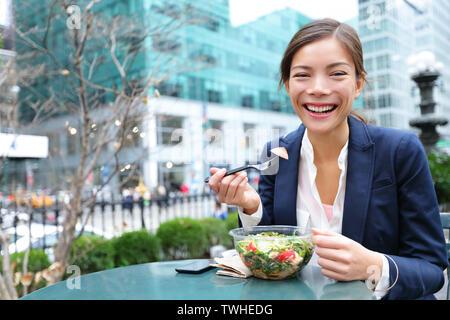 Business Woman eating salad sur pause déjeuner dans le parc de la ville vivre un mode de vie sain. Happy smiling young businesswoman multiraciale, Bryant Park, à Manhattan, New York City, USA Banque D'Images