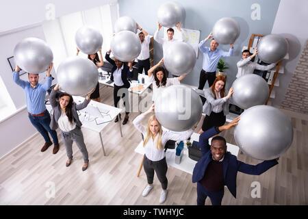 Happy Group Of Businesspeople étendant leurs bras à l'aide de l'Office de remise en forme Banque D'Images