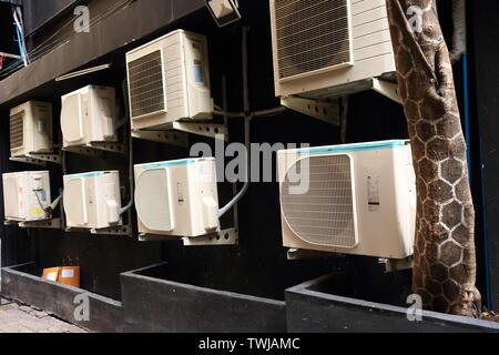 Groupe d'unités de condensation des climatiseurs fixés au mur derrière l'immeuble, selective focus Banque D'Images