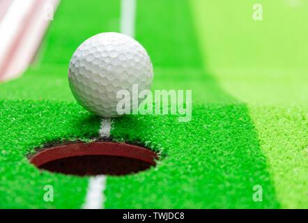 Balle de golf sur la lèvre du tasse, concept objectif Banque D'Images