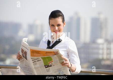 Femme d'affaires lisant un journal et souriant Banque D'Images