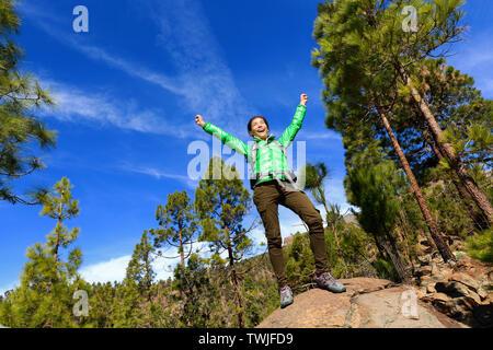 Randonnées woman reaching haut sommet cheering célébrant en montagne avec les bras tendus vers le ciel. Happy female hiker.