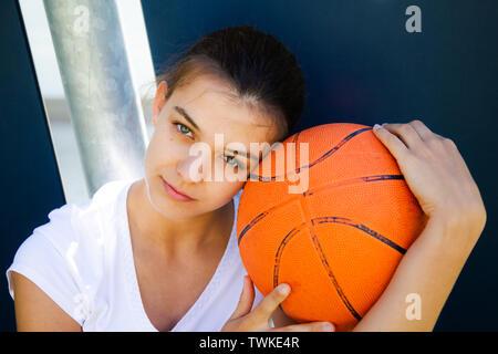 Portrait d'une belle et jeune joueur de basket-ball féminin de la face en appui sur la balle Banque D'Images