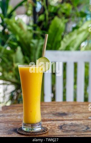 Le jus de mangue dans un grand verre avec paille de bambou, décoré avec de la chaux.