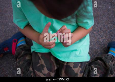 Les enfants mal à son doigt, garçon avec douleur qu'il s'est blessé au doigt l'image haute résolution galerie. Banque D'Images
