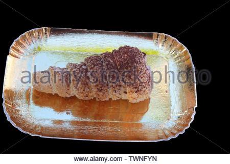 L'italien la pâte feuilletée remplie de crème glacée servie sur assiette en papier doré isolé sur fond noir Banque D'Images