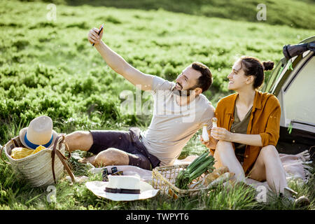 Les jeunes et joyeux couple photo selfies lors du pique-nique à le camping, les voyages en montagne au coucher du soleil Banque D'Images