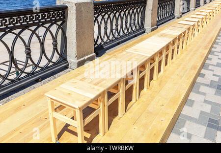 Tabourets en bois sans dossier stand dans une rangée sur le remblai de la ville Banque D'Images