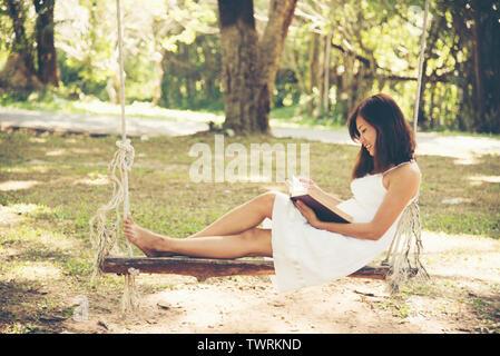 Détente femme lisant un livre dans le parc Banque D'Images
