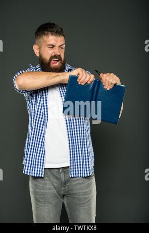 Je déteste ce livre. Hipster en colère avec livre sur fond gris. Homme barbu livre déchirant avec colère. Rencontrez des problèmes avec la tâche difficile dans le livre. Banque D'Images