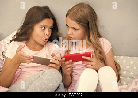 Les enfants jouent le jeu mobile smartphone application. Application Smartphone concept. Loisirs fille soirée pyjama. Les filles peu smartphone blogueurs. Découverte de réseau social. Divertissement pour Smartphone.