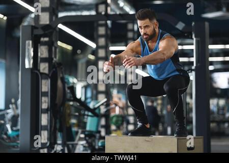 Faire de l'athlète de saut à l'exercice de gym Banque D'Images
