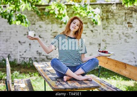 Portrait of young woman sitting on wooden table in garden holding bol de fruits et un verre de yaourt Banque D'Images