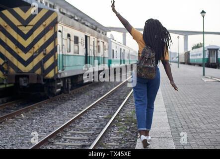 Vue arrière du jeune femme au bord du rail à la gare Banque D'Images