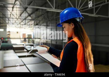 Travailleur féminin vérifier les documents en usine-entrepôt