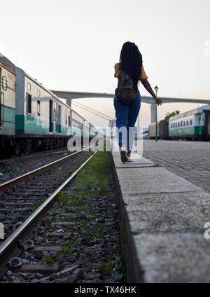 Vue arrière du jeune femme marchant au bord du rail à la gare Banque D'Images