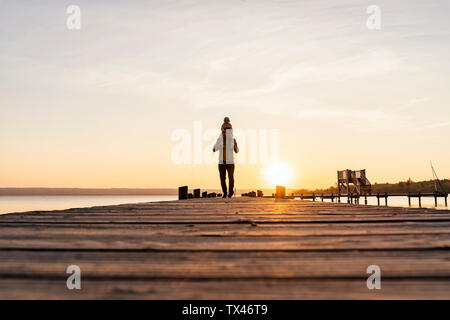 Allemagne, Bavière, Ostfildern, father carrying daughter on shoulders on jetty at sunset Banque D'Images