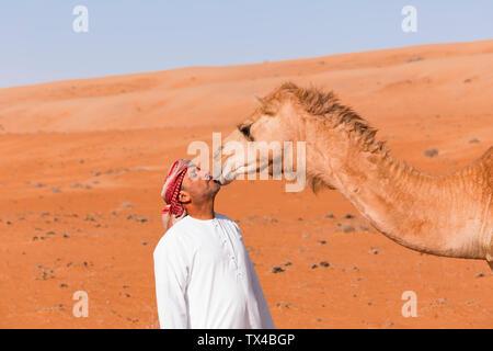 Le Bedouinn embrasse son chameau dans le désert Wahiba Sands, Oman Banque D'Images