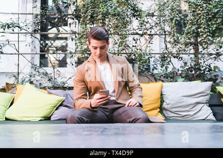 Young man sitting on couch in a cafe using cell phone Banque D'Images