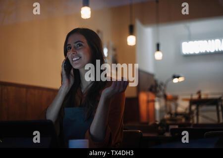 Jeune femme assise à table dans un restaurant avec un téléphone mobile et tablette