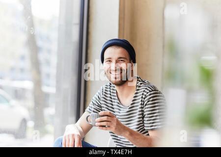 Portrait of smiling young man holding Coffee cup à la fenêtre Banque D'Images