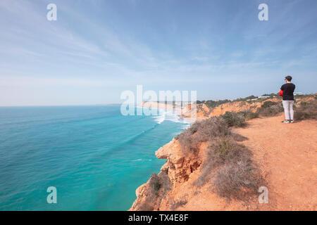 Portugal, Algarve, Lagos, Ponta da Piedade, l'homme debout à la côte à la recherche de la mer Banque D'Images