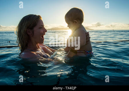 Polynésie Française, Tahiti, Papeete, femme jouant avec son petit bébé dans une piscine à débordement au coucher du soleil