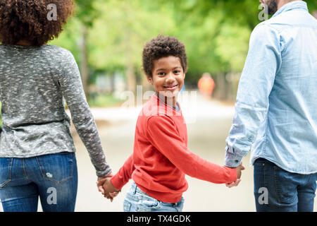 Happy boy holding parent's hands, walking in a park Banque D'Images