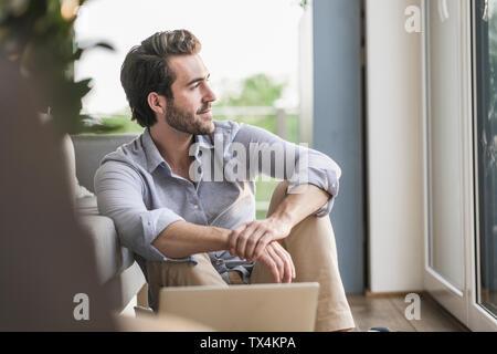 Jeune homme assis à la maison sur le plancher, en utilisant un ordinateur portable, à la fenêtre de