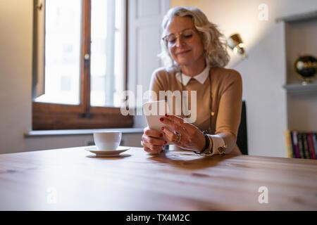 Young businesswoman sitting at table avec tasse de café using smartphone
