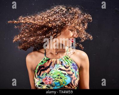 Souriante jeune femme rejetant ses cheveux bouclés en face de fond sombre