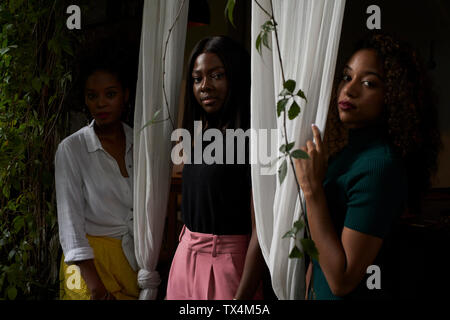 Portrait de trois femmes debout entre les rideaux Banque D'Images