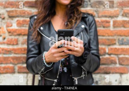 Jeune femme portant veste en cuir noire, en utilisant smartphone, mur de brique à l'arrière-plan
