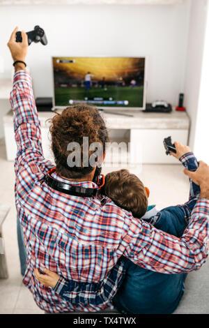 Vue arrière de l'heureux père et fils assis ensemble à la table de jeu d'ordinateur de jeu Banque D'Images