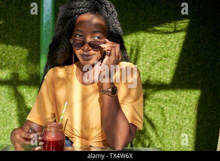 Jeune femme avec des dreadlocks ayant un smoothie dans un café
