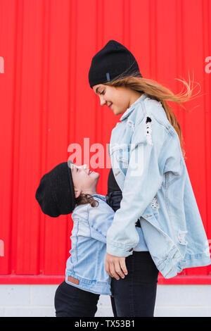 Happy little girl embrassant sa soeur en face de fond rouge Banque D'Images